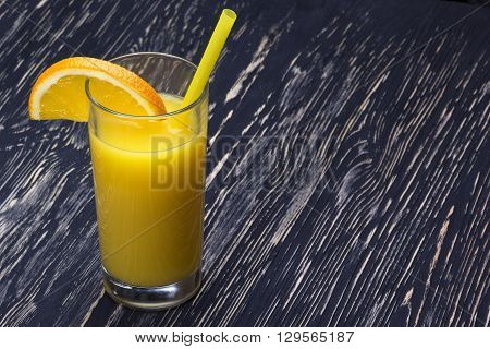 Orange juice in the glass on black wooden table