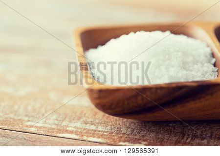 food, junk-food, cooking and unhealthy eating concept - close up of white sea salt heap in wooden bowl