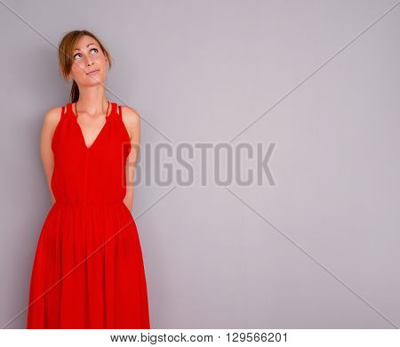 female in red dress thinking