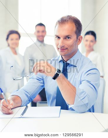 businessman with glasses writing in notebook in office