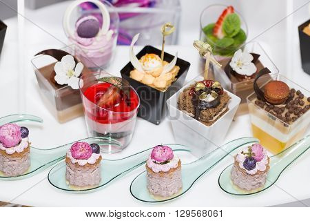 mini canapes in plastic cups decorated with edible flowers