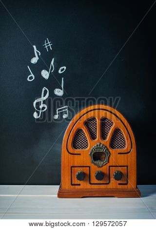 Retro Radio on a dark background with musical notes on a blackboard