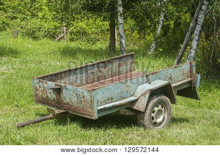 Obsolete weathered metal lightweight cargo trailer platform in farmyard