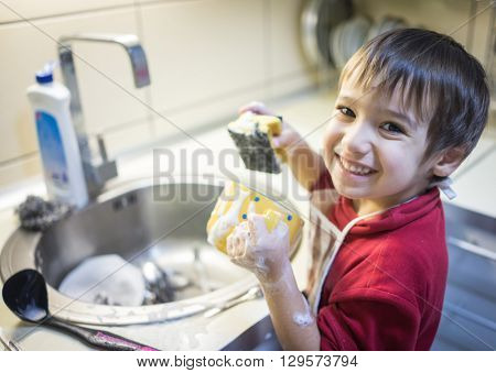 A little cute boy washing dishes