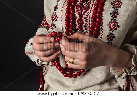 Red beads in hands. Ukrainian embroidery. Rosaries.
