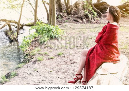 young woman sitting on a tree by the water wrapped in a red blanket