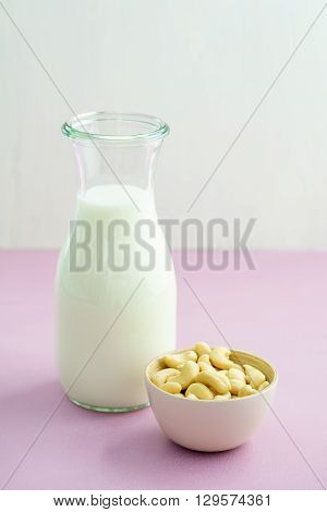 Fresh homemade cashew milk in a bottle with fresh cashews