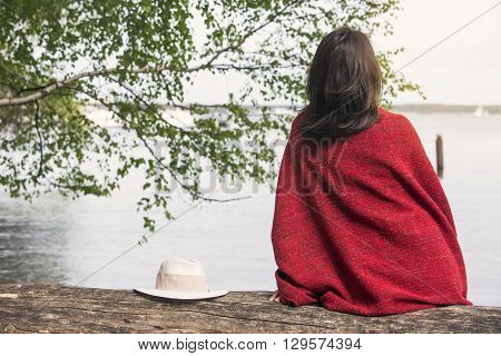backside of young woman sitting on tree wrapped in a blanket in front of a lake