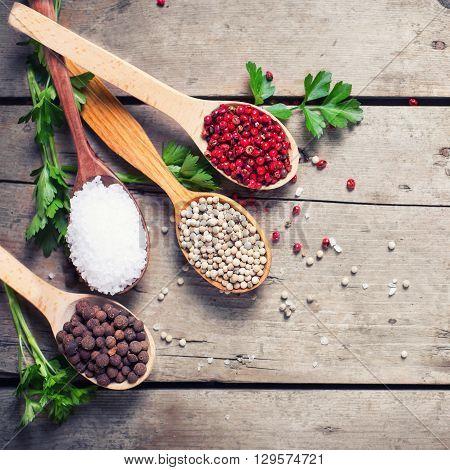 Seasoning for cooking. Red white and allspice pepper and sea salt in wooden spoon on aged wooden background. Food ingredient. Selective focus. Flat lay. Top view. Square image.