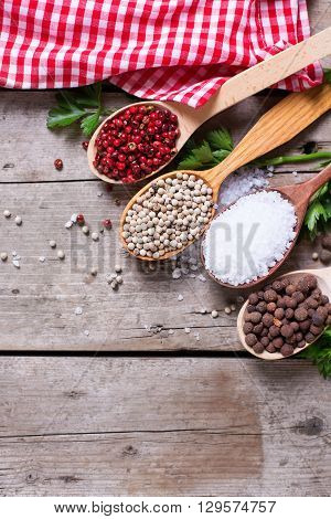Seasoning for cooking. Red white and allspice pepper and sea salt in wooden spoon on aged wooden background. Food ingredient. Selective focus. Place for text. Flat lay. Top view. Vertical image.