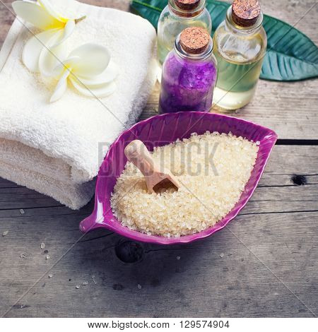 Spa setting. Sea salt in bowl in form of leaf with towels and bottles with oil on vintage wooden background. Selective focus is on towels. Place for text. Square image.