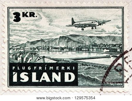 ISLAND - CIRCA 1947: A stamp printed by ISLAND shows The Esja massif seen from Reykjavik's old city center. Aircraft over Reykjavik circa 1947