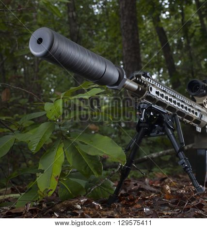 Silencer at the end of a sniper rifle in a forest