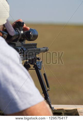 Shooter behind a rifle changing elevation for a long shot