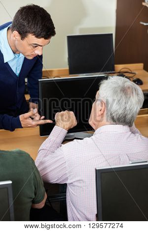 Tutor Discussing With Senior Man In Computer Class