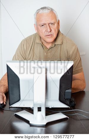 Serious Senior Man Using Computer At Desk In Class