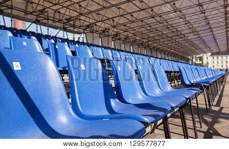 plastic blue seats in a stadium outside closeup