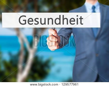 Gesundheit (health In German) - Businessman Hand Holding Sign