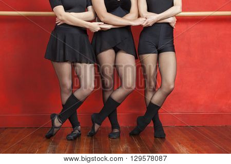 Low Section Of Ballerinas Holding Hands