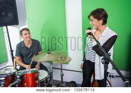 Woman Singing While Looking At Drummer