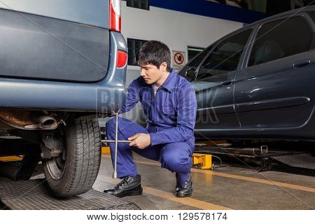 Technician Using Rim Wrench To Fix Car Tire