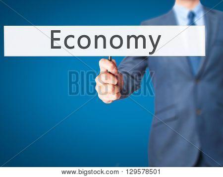 Economy - Businessman Hand Holding Sign