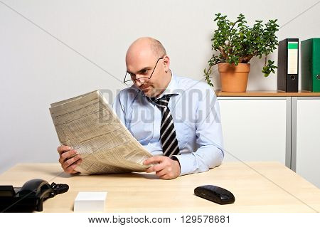 Manager Studies The Financial Part Of A Newspaper.