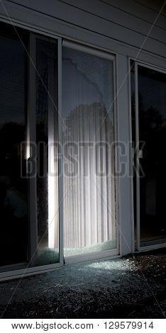 Shattered sliding glass door after a burglar broke in