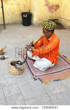 JAIPUR INDIA - NOVEMBER 2 2015: Snake charmer. Man plays his pungi to charm a cobra outside the Jantar Mantar monuments in India.