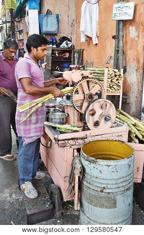 JAIPUR INDIA - NOVEMBER 13 2015: Squeezing sugar cane. Men extract the juice from sugar cane in an alley in Jaipur.