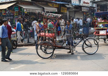 NEW DELHI INDIA - OCTOBER 27 2015: Crowded street scene in New Delhi with pedicab. Pedicabs are a source of income for many people in Asia.
