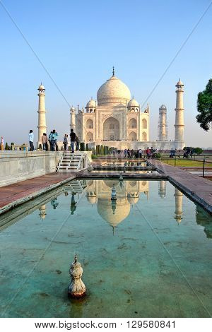AGRA INDIA - 31 OCTOBER 2015: Tourists at the Taj Mahal. The temple is reflected in one of the the ponds.