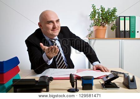 Manager explains a state of affairs. He sits in his office