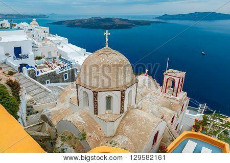 Fira, modern capital of the Greek Aegean island, Santorini, with orthodox church, caldera and volcano, Greece