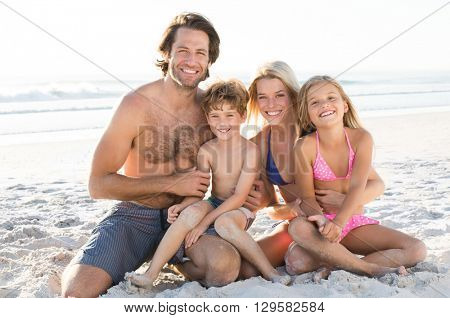 Young happy family in swimsuit at beach looking at camera. Young couple with children at beach in summer holiday. Children playing with sand at beach with their parents.