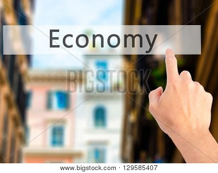 Economy  - Hand Pressing A Button On Blurred Background Concept On Visual Screen.