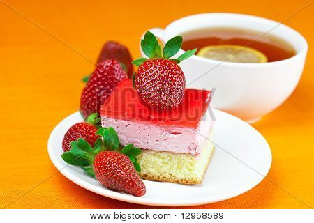 Lemon Tea, Cake And Strawberries Lying On The Orange Fabric