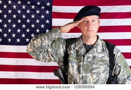Veteran soldier facing forward saluting with USA flag in background. Soldier armed with military pistol and ammo clips.