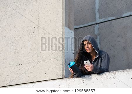 Sporty Woman Texting On Smartphone After Urban Workout