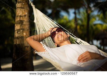 Tranquil woman relaxing lying on a hammock at tropical beach. Summer vacation relax and tranquility concept. Relaxed female resting outdoor.