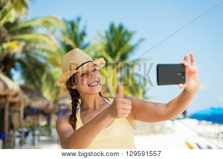 Woman on summer tropical caribbean travel taking selfie photo. Young happy brunette on beach vacation using her smartphone camera for self portrait with palm trees on background.