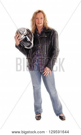 A middle age woman standing in jeans holding her motorcycle helmet in a leather jacket isolated for white background.