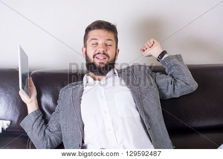 sleepy bearded business man yawning at the sofa