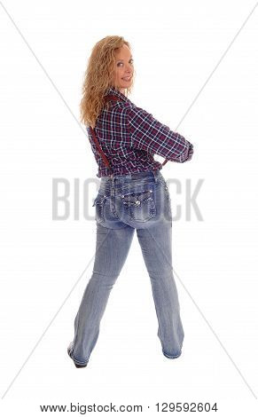 A lovely blond woman in jeans and checkered shirt standing from the back looking over her shoulder isolated for white background.