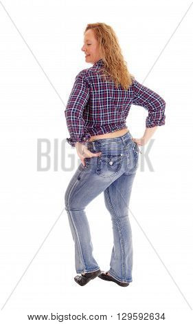 A portrait image of a blond middle age woman in jeans and a checkered shirt looking over her shoulder isolated for white background.