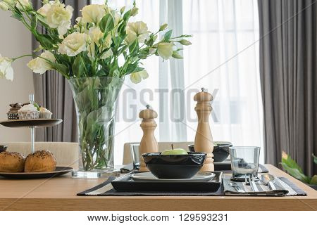 table set on wooden dinning table in dinning room with vase of flower