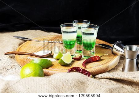 three alcoholic drinks shot on a wooden board with fruit