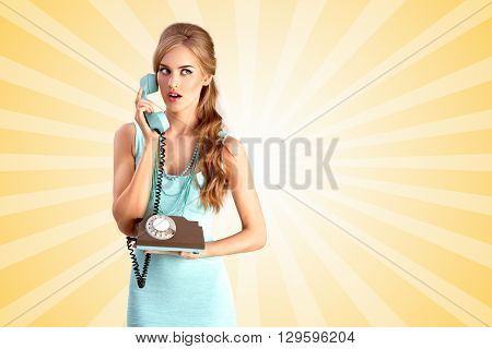 Creative photo of a pretty pin-up girl speaking via vintage phone on colorful abstract cartoon style background.