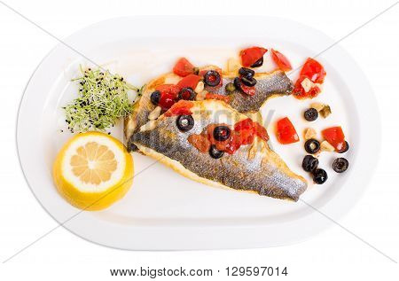 Fillet of seabass on a baked potato with capers and tomatoes. Isolated on a white background.