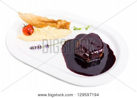 Beef medallion in chianti sauce with potato puree and dried jamon. Isolated on a white background.